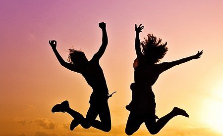 2 silhouettes jumping and cheering in front of sunset