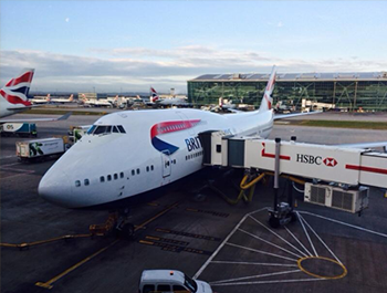 747 operated by British Airways, connected to a loading bridge