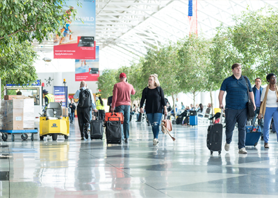 Interior shot of Charlotte Airport, showing a bright space, with green plants and people walking with suitcases
