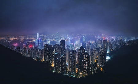 Birds eye view of skyscrapers in busy city at night