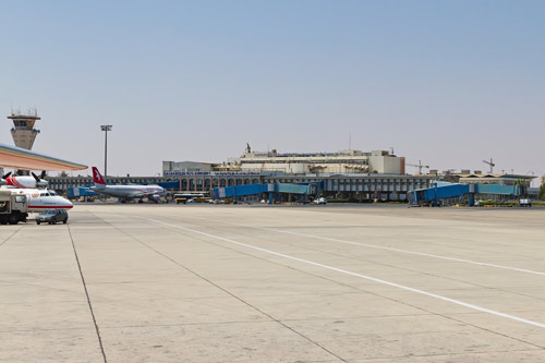 exterior shot of damascus international airport showing control tower in background and planes on tarmac in foreground