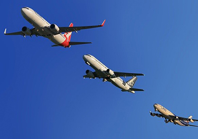 Different airlines flying in the sky in a line