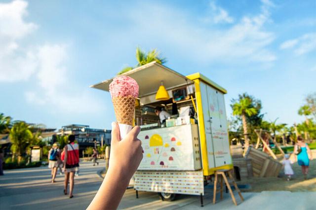 Person holding up strawberry ice cream cone
