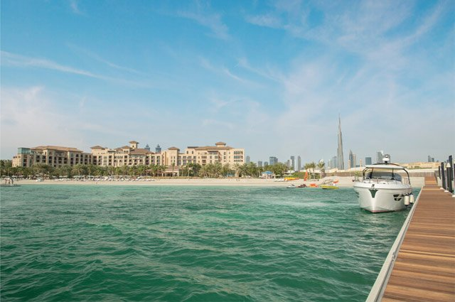 Boat in sea at Dubai with city in the background