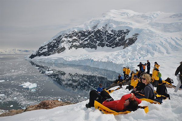 People laying on snow in Antarctica