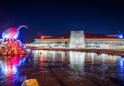 KEF airport exterior shot, showing a modern glass terminal building lit up by colourful lights and LED's at night