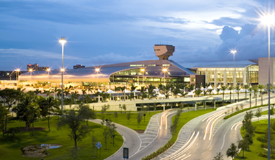 Miami International Airport exterior shot, showing the modern main terminal building lit up at dusk