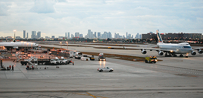 A view out over the runway, with planes on tarmac and Miami skyline in the background