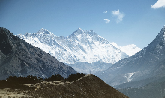 wide shot of Mt Everest, showing the snow capped peaks of the mountain against blue sky
