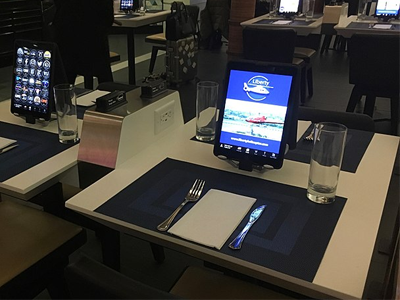 A terminal restaurant table with i-pad built into the table so passengers can monitor flights