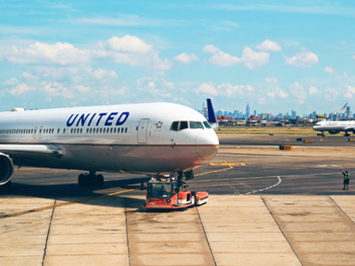 A united Airlines plane on the runway tarmac of Newark International Airport, on a bright sunny day with city skyline in background