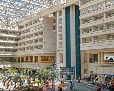 Main airport building interior, showing a modern light atrium, with multiple levels around the 'courtyard' space and palm trees on the ground floor
