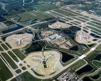 Birds eye view of the airport, showing the main terminal and four airside concourses