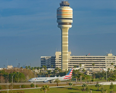 Orlando International Airport exterior shot, with plane on tarmac in front of building