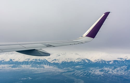 Plane wing flying over mountains