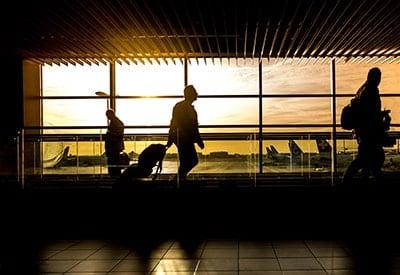 Man walking through an airport at sunset