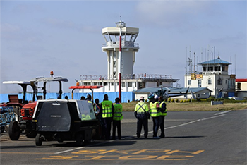 Exterior shot of Wilson terminal, showing agents in high-vis jackets on the tarmac and a small control tower