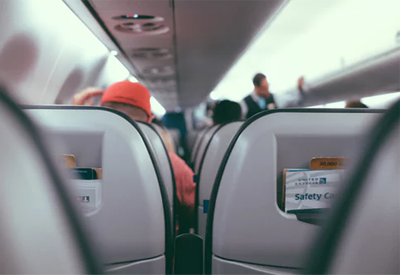 view though the gap between airplane seats, showing flight attendant talking to passengers