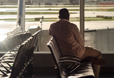 Man say in airport waiting area looking out at plane on tarmac