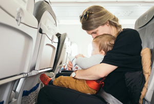 mother with baby on her lap on a plane seat