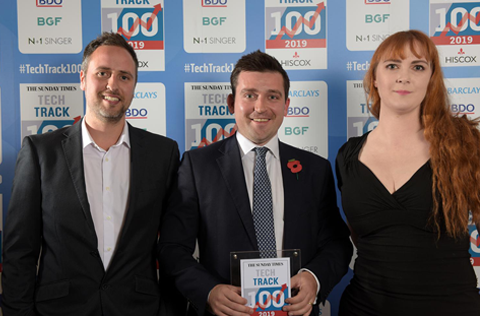 Photo taken at the Tech Track 100 Awards Dinner in London, showing Sam Argle (the managing director of Alternative Airlines) with the company's SEO and Development managers, holding the award plaque