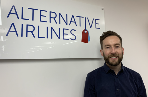Head shot of Alternative Airlines new Airline Relationship Manager, Thomas Garrett, standing in front of an 'Alternative Airlines' sign