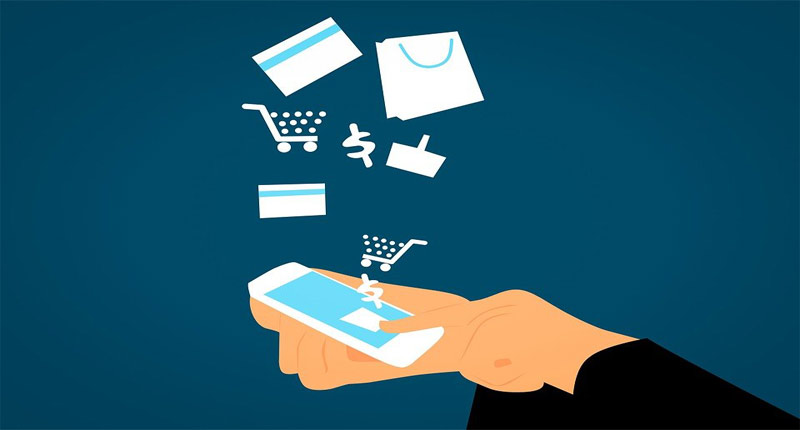 Image of hand using a mobile device with other images credit cards and shopping trolley